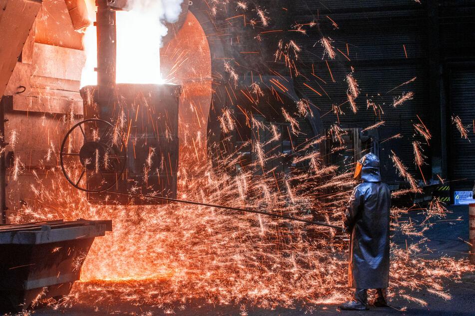 Ein Arbeiter mit Schutzmantel und Helm steht vor sprühenden Funken und kontrolliert die Abfüllungen in einen Transporttopf. In der Eisengießerei Torgelow (EGT) GmbH werden erneut Vertreter der Schweriner Landesregierung erwartet.