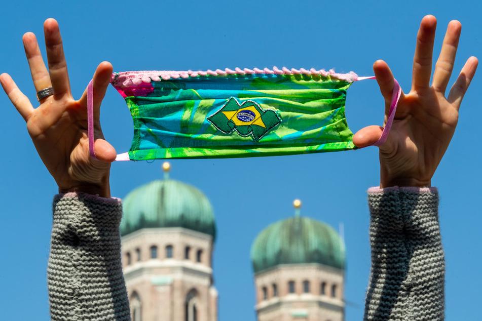 Eine Frau hält für ein Foto eine selbstgenähte Mundschutzmaske in die Luft. Im Hintergrund sind die Türme der Münchner Frauenkirche zu sehen.