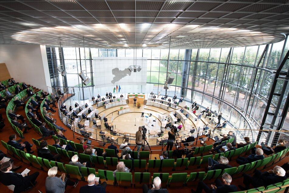 Besucher und Abgeordnete sitzen im Sächsischen Landtag auf ihren Plätzen.