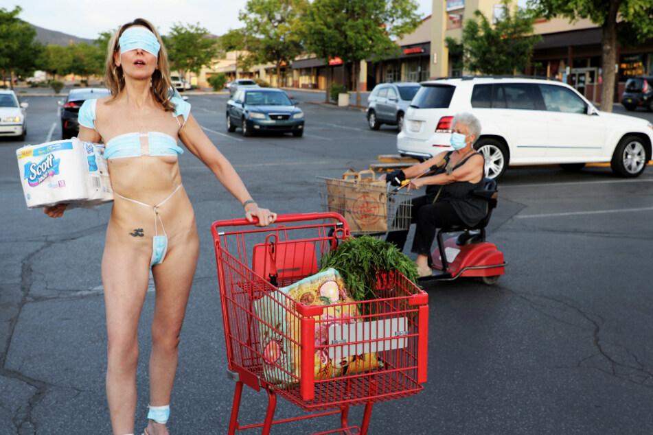 Mit einem Bikini aus Mundschutzmasken protestiert DaVida Sal vor einem Supermarkt.