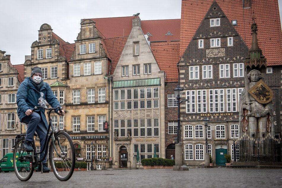 Ein Mann, der aufgrund der Corona-Pandemie eine Mundschutzmaske trägt, fährt auf einem Fahrrad über den leeren Bremer Marktplatz.
