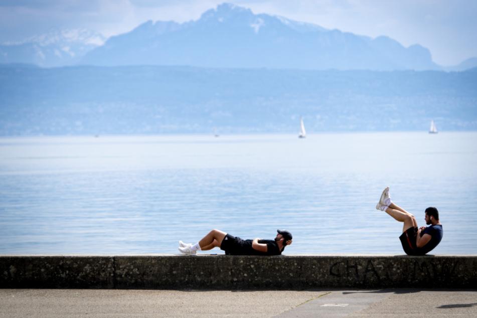 Zwei Männer machen Sportübungen am Ufer des Genfer Sees und halten dabei das Abstandsgebot während der Corona-Krise ein.