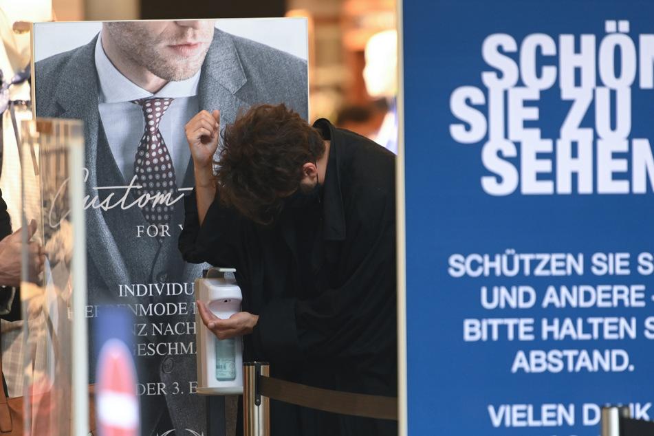 Kunden desinfizieren ihre Hände am Eingang eines Textilgeschäfts. (Archivbild)