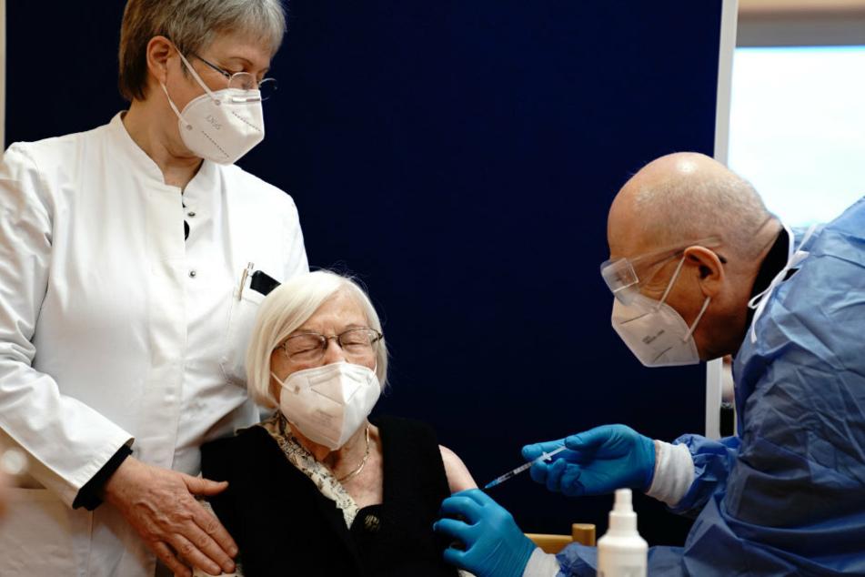 Die 101-jährige Gertrud Haase (M) wird im Pflegeheim Agaplesion Bethanien Sophienhaus von Impfarzt Fatmir Dalladaku (r) gegen das Coronavirus geimpft, Irmgard Landgraf Ärztin steht links.