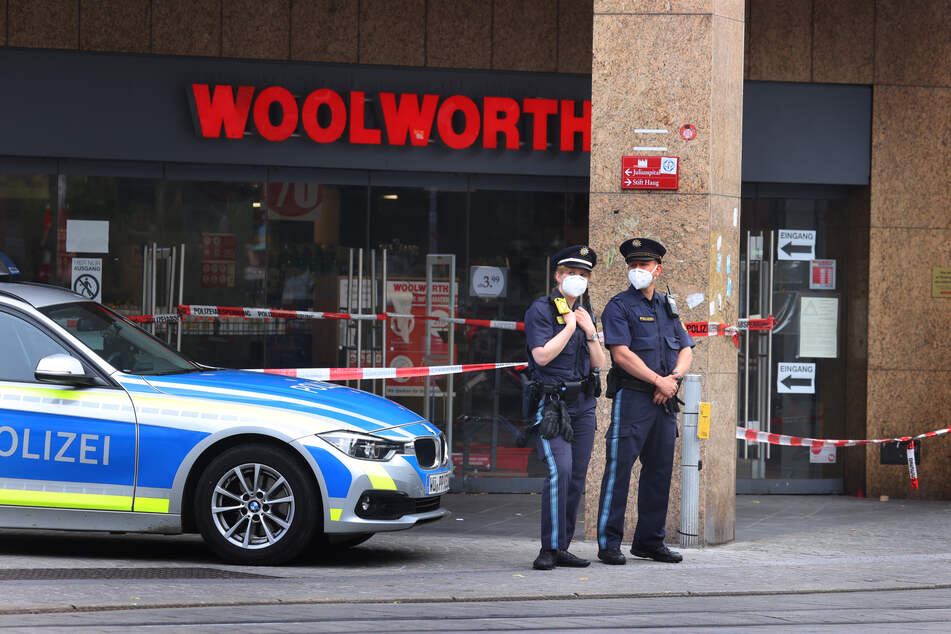 Polizeibeamte stehen vor der Filiale der Einzelhandelskette Woolworth, in der Innenstadt von Würzburg. Dort begann am Freitag das blutige Massaker.