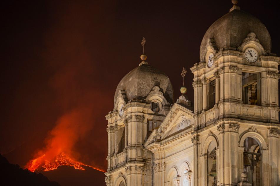Lava bricht aus einem Krater des Ätna, dem größtem aktiven Vulkan in Europa, hinter der Kirche Santa Maria della Provvidenza aus.