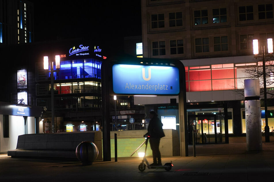 Ein E-Tretrollerfahrer ist am späten Abend kurz nach 22 Uhr auf dem Alexanderplatz unterwegs.