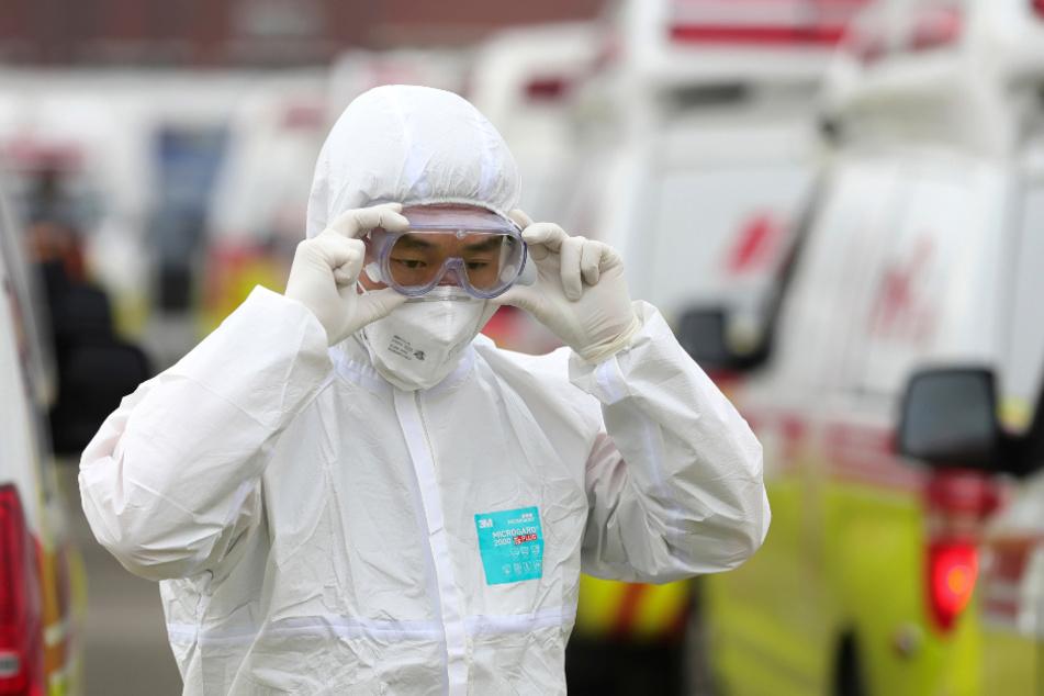 Ein Rettungssanitäter in einem Schutzanzug passt seine Schutzbrille an.