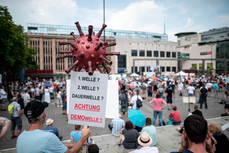 Ein Teilnehmer der Demonstration hält ein Schild mit einem Coronavirus-Symbol in die Höhe.