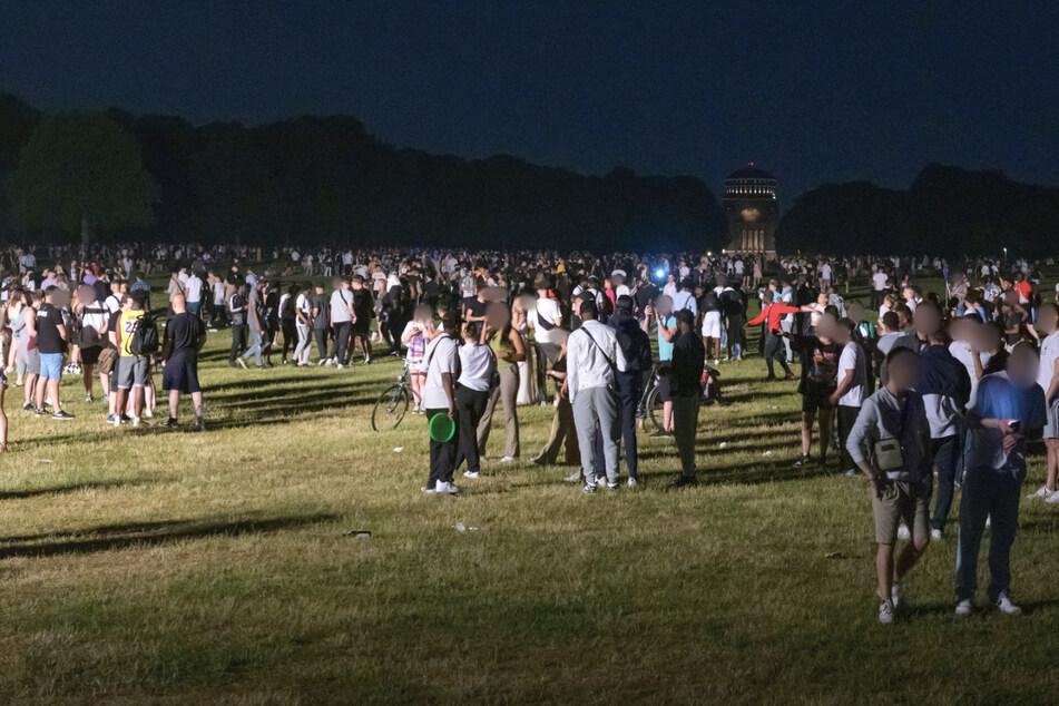 Kleinere und größere Menschengruppen stehen auf der Stadtpark-Wiese im Schein des von der Polizei aufgestellten Lichtmastes.