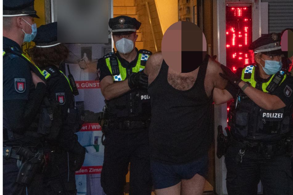Die Polizei führt einen Mann in Boxershorts und Unterhemd ab.