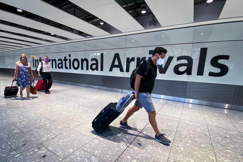 Passagiere gehen durch die Ankunftshalle des Londoner Flughafens Heathrow.