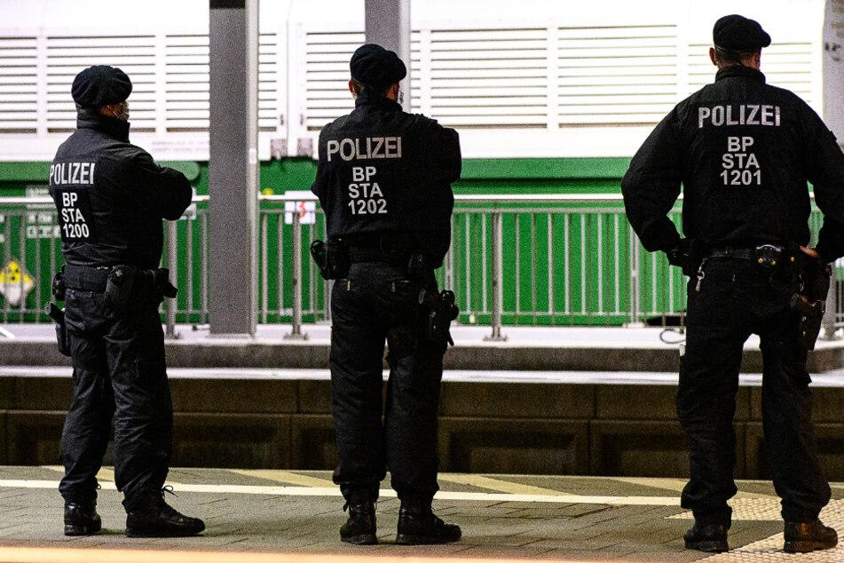 Einsatzkräfte der Bundespolizei stehen auf einem Bahnsteig vor einem von insgesamt sechs Castor-Behältern im Bahnhof von Hünfeld.