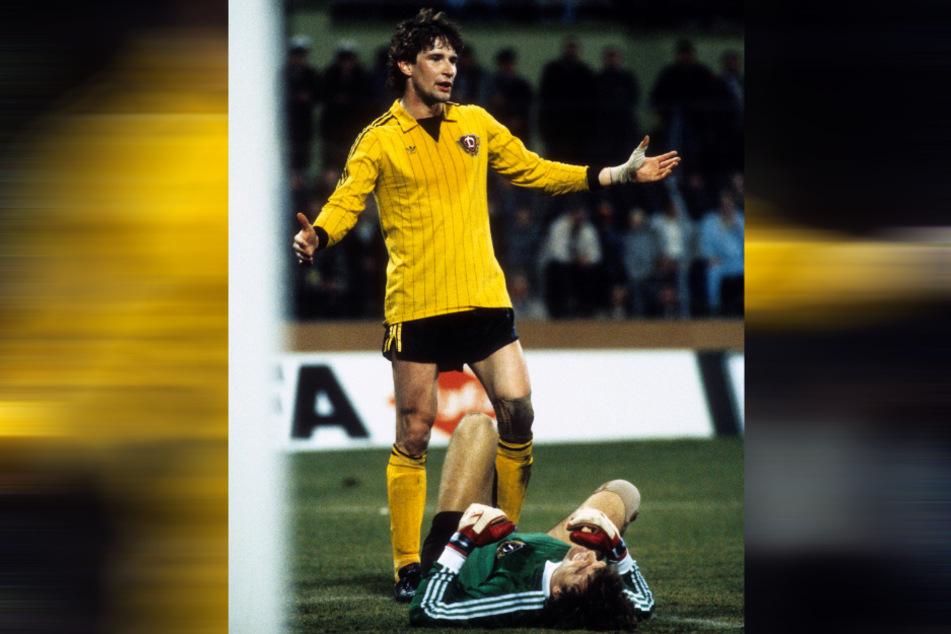 Eine der entscheidenden Szenen des Spiels: Nach einem bösen Foul von Funkel liegt Dynamo-Schlussmann Bernd Jakubowski verletzt am Boden und muss zur Pause ausgewechselt werden. Andreas Trautmann reklamiert.