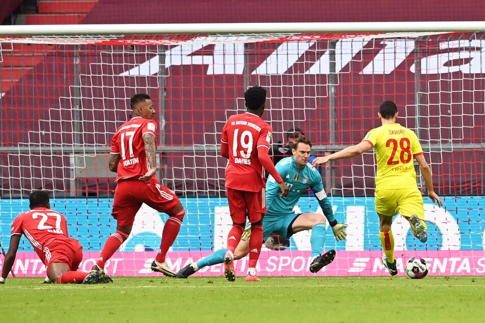 Kölns Ellyes Skhiri (r.) erzielt gegen Münchens Torwart Manuel Neuer das Tor zum 1:2-Anschluss für den 1. FC Köln.