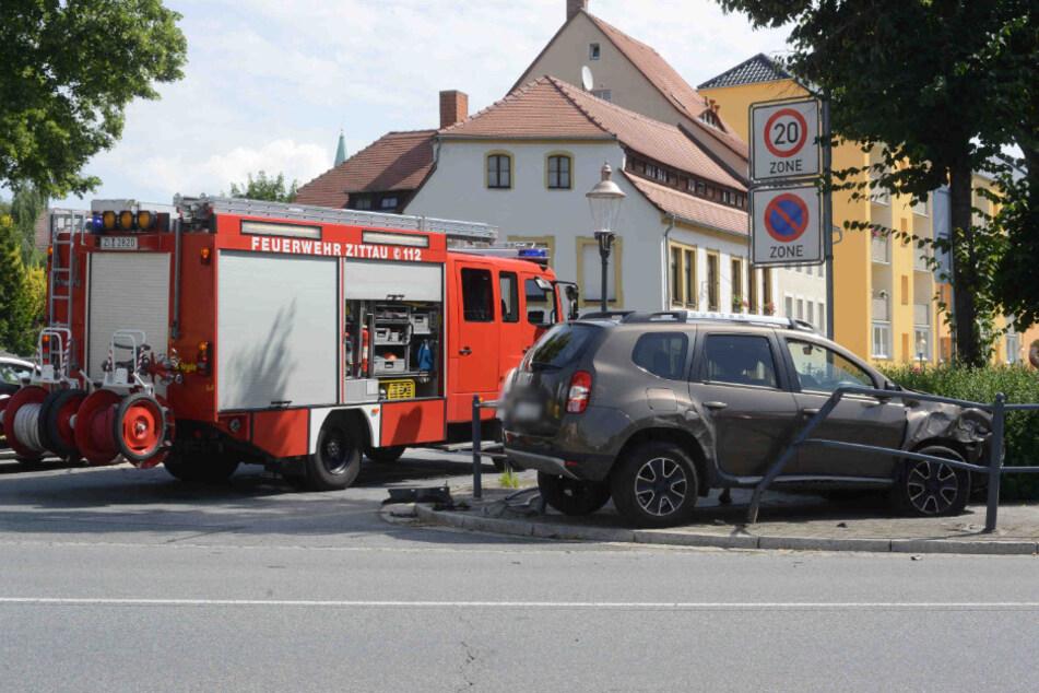 Der Dacia steht auf dem Fußweg und ist vom Unfall gezeichnet.