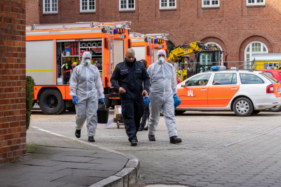 Zwei Mitarbeiter in Schutzanzügen folgen dem Sicherheitspersonal in der Feuerwache.