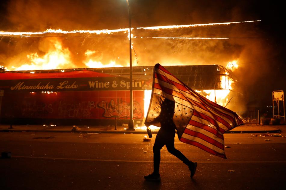 Ein Demonstrant trägt neben einem brennenden Gebäude eine US-Flagge während der Proteste nach dem Tod von George Floyd, der in Folge einer brutalen Festnahme durch einen Polizisten in Minneapolis starb.