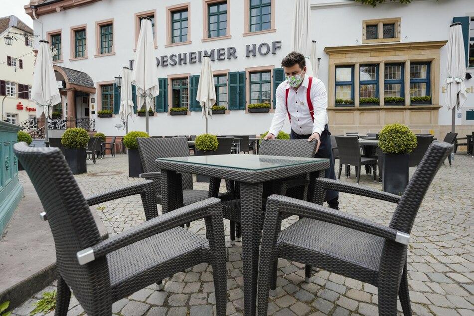 """Ein Mitarbeiter stellt Stühle an einen Tisch im Aussenbereich vor dem Restaurant und Hotel """"Deidesheimer Hof""""."""