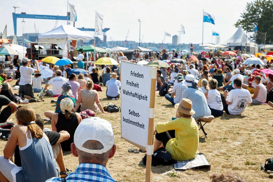 """Ein Teilnehmer der Demonstration """"Freiheit und Selbstbestimmung"""" auf der Reventlou-Wiese hält ein Transparent mit der Aufschrift """"Frieden Freiheit Wahrhaftigkeit Selbstbestimmung""""."""