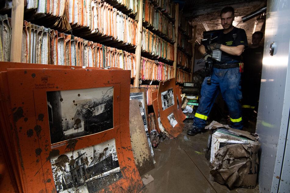 Ein Helfer des Technischen Hilfswerks (THW) läuft durch das überflutete Stadtarchiv von Stolberg.
