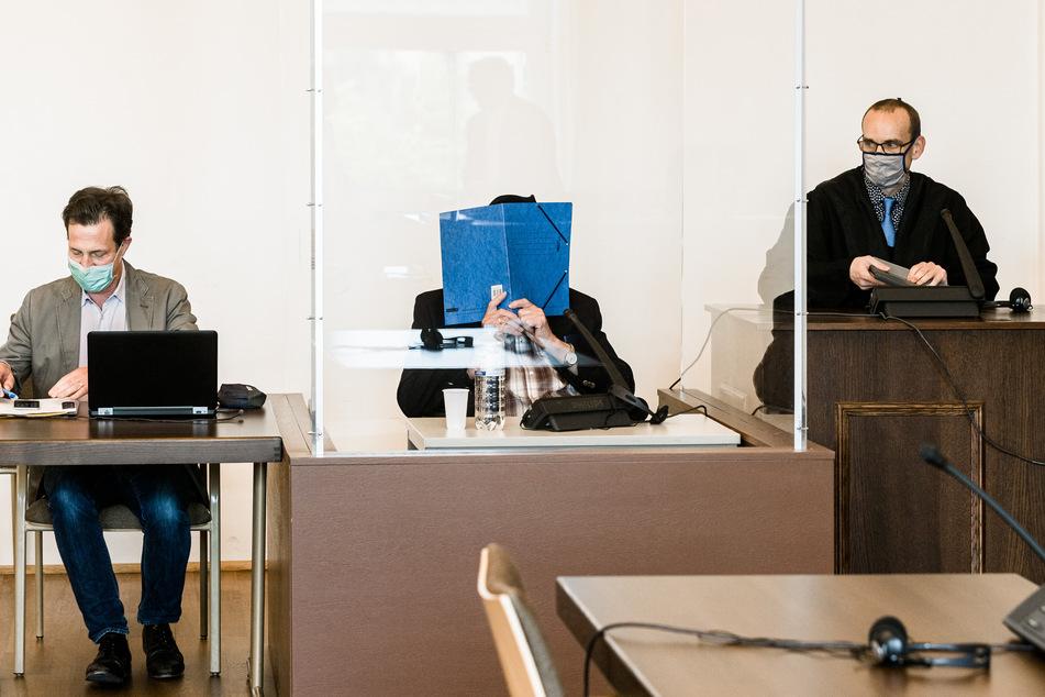 Der Angeklagte sitzt zu Beginn des Prozesses zwischen einem Arzt (links) und seinem Anwalt.