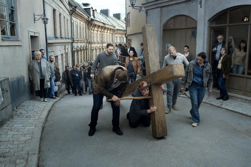 """Ein Albtraum. Ein Mann wird vom """"Pöbel"""" durch das Dorf getrieben. Er muss ein Kreuz halten und wird immer wieder ausgepeitscht. Einer der grausamen Aspekte des Films und menschlichen Lebens."""