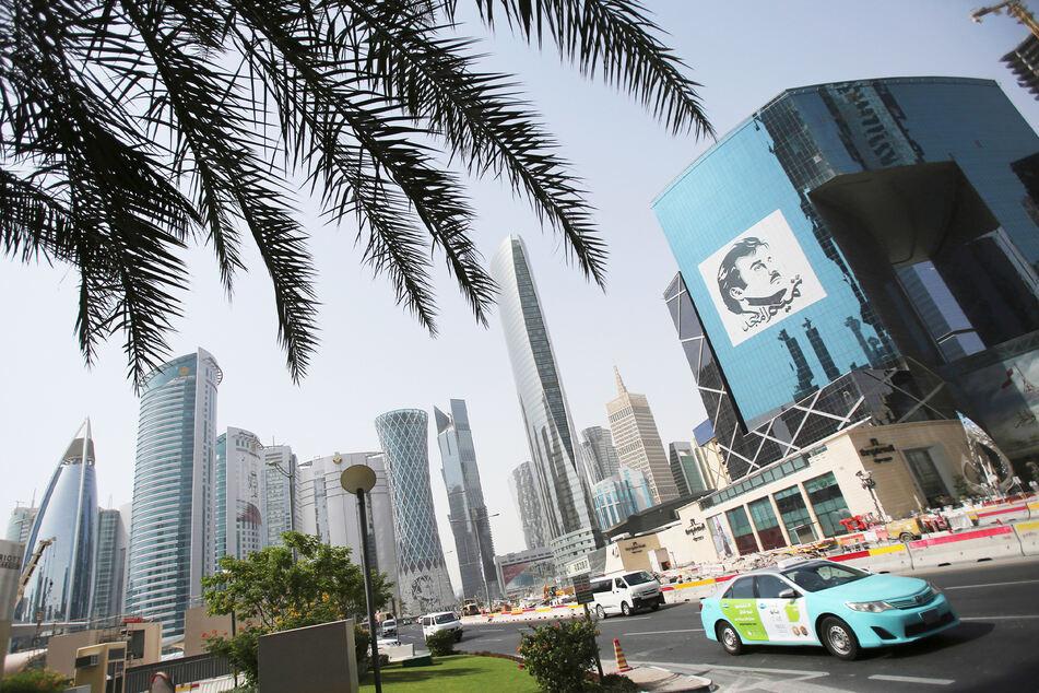 Ein Taxi fährt an einem Gebäude mit einem Bild des Emirs von Katar, Sheikh Tamim bin Hamad Al Thani, vorbei.