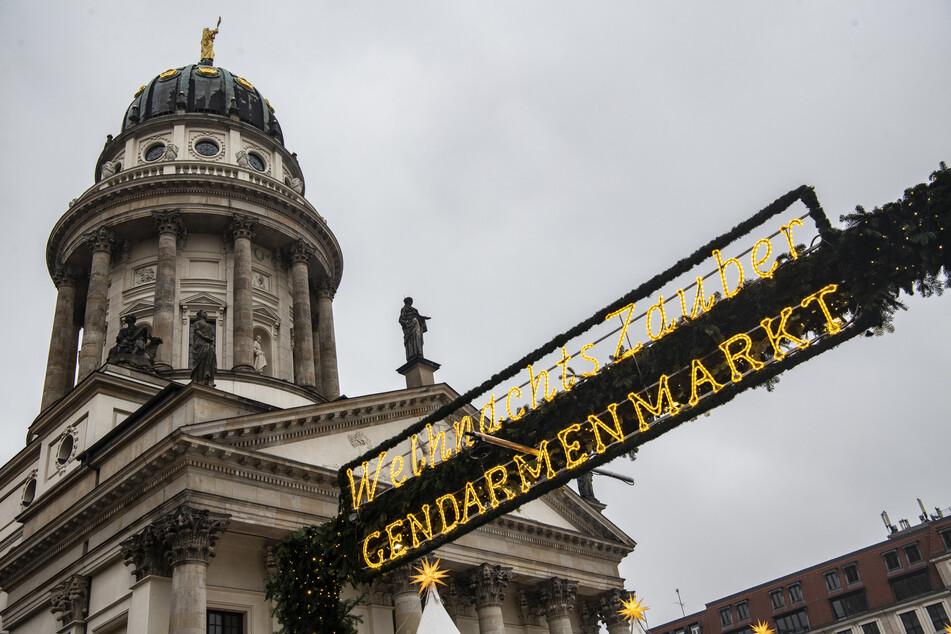 """Eine Dekoration mit der Aufschrift """"WeihnachtsZauber Gendarmenmarkt"""" hängt über einem der Eingänge zum Weihnachtsmarkt auf dem Gendarmenmarkt."""