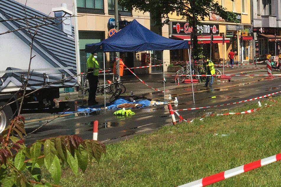 Unter einem Pavillon liegt die Leiche der Radfahrerin, die mit Tüchern abgedeckt worden ist.