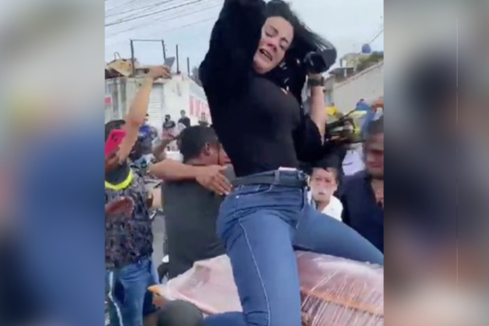 The lady jumps up on the coffin and starts dancing.