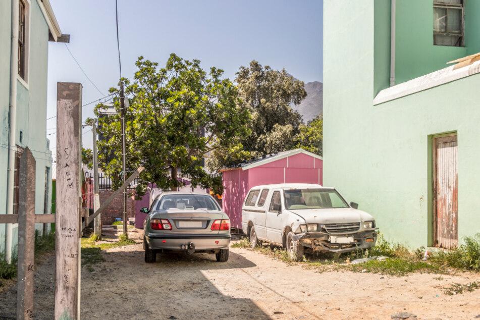 Südafrika: Zwei alte und zum Teil schrottreife Gebrauchtwagen stehen in einem Stadtviertel von Kapstadt.