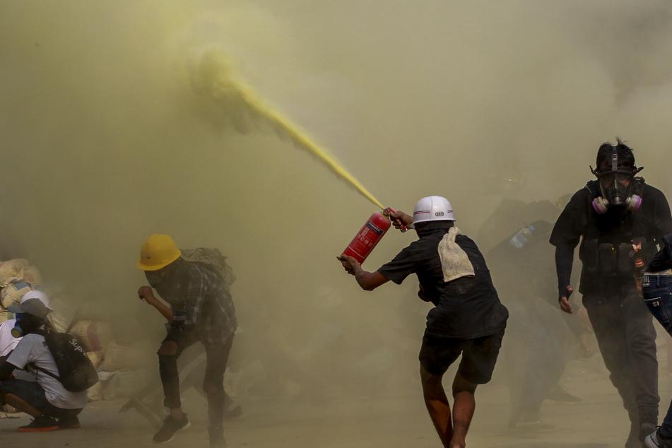 Demonstranten in Yangon benutzen einen Feuerlöscher zum Schutz vor Einsatzkräften. Auch am Mittwoch gingen landesweit Tausende gegen die Generäle auf die Straße.