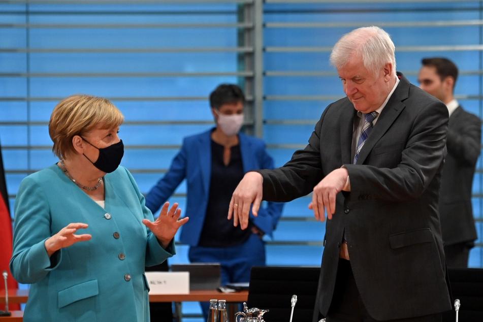 Bundeskanzlerin Angela Merkel spricht mit Horst Seehofer (CSU, r), Bundesinnenminister, bei dessen Ankunft zu einer Sitzung des Kabinettsausschusses zur Bekämpfung von Rechtsextremismus und Rassismus.