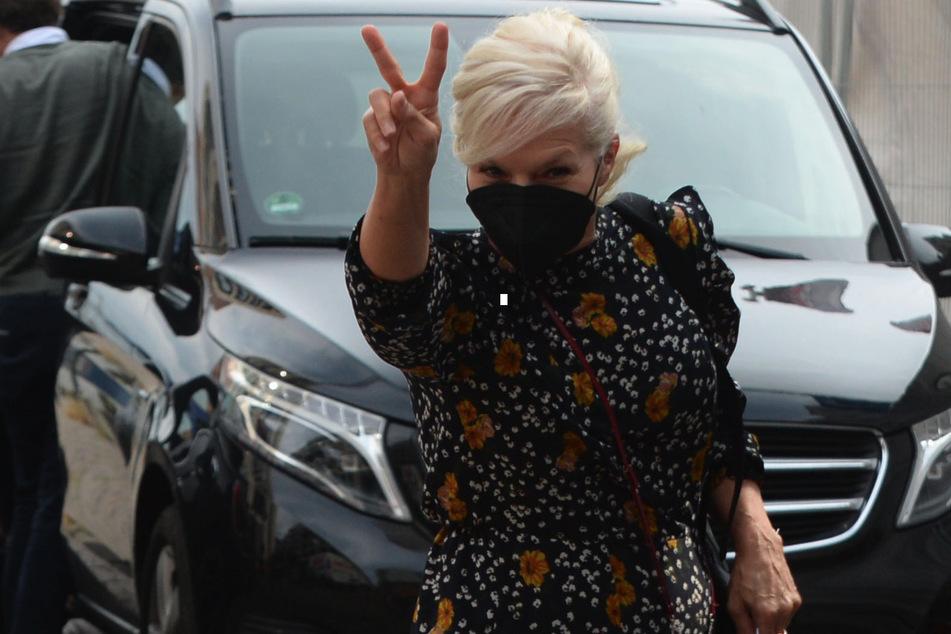 """Ina Müller (55) kommt """"Zum Schellfischposten"""" und zeigt das Victory-Zeichen."""