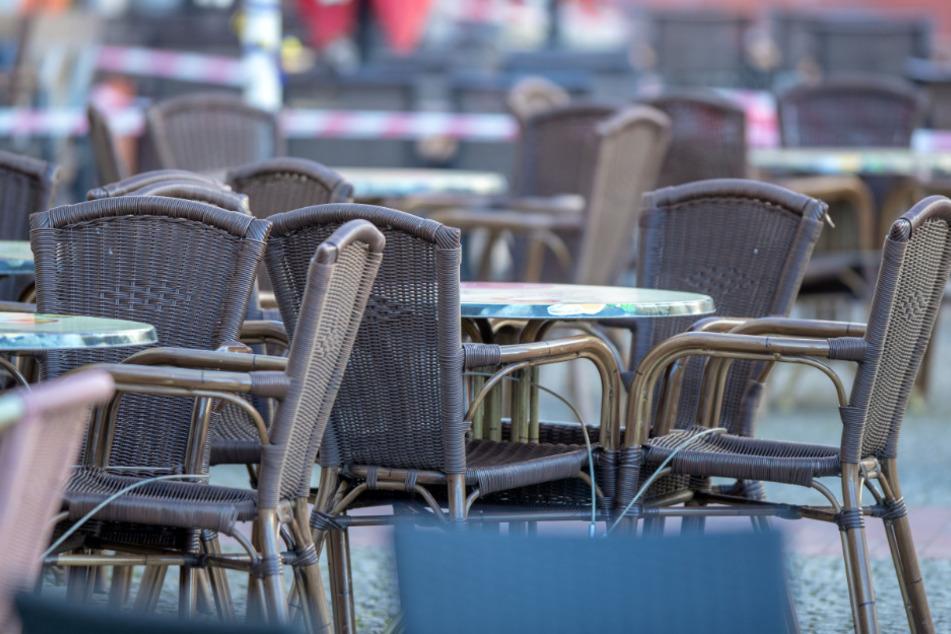 Leere Stühle und Tische stehen in einem geschlossenen Straßencafe.