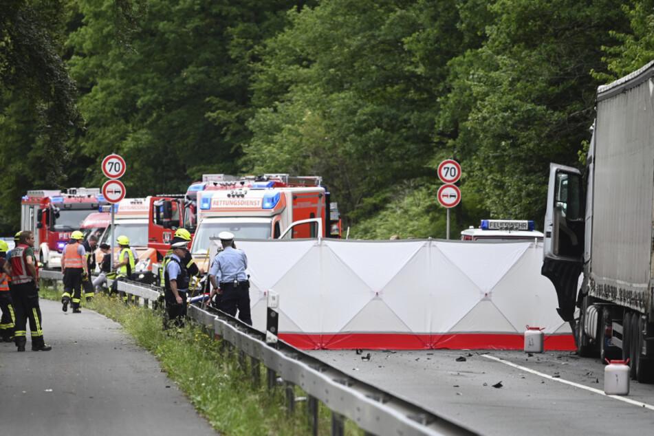 Feuerwehrleute arbeiten an einer Unfallstelle hinter einer Sichtschutzwand.