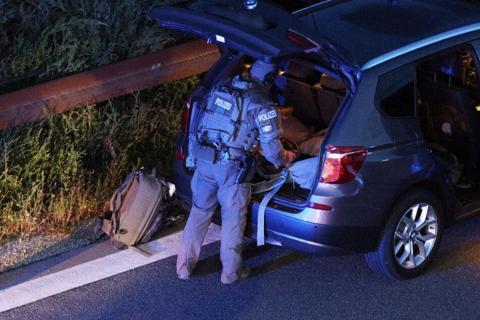 Ein Polizist mit Spezialausrüstung steht an einem Fahrzeug auf der Autobahn 9. Die Polizei war aufgrund einer möglichen Bedrohungslage mit einem Großaufgebot vor Ort.