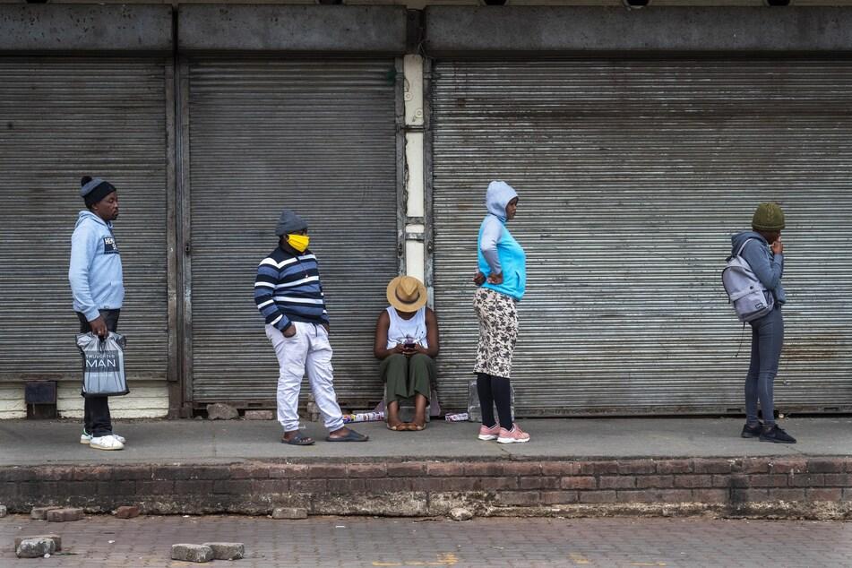Kunden stehen unter Einhaltung eines Sicherheitsabstandes vor einem Supermarkt in Alexandra (Südafrika) Schlange.