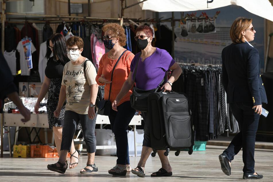 Frauen tragen Mund-Nasen-Schutz während sie durch die Innenstadt gehen.