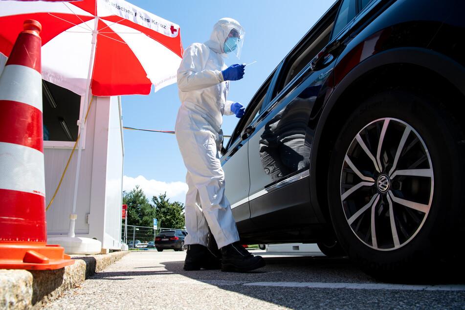 Mitarbeiter vom Bayerischen Roten Kreuz nehmen an einem Corona-Testzentrum an der Autobahn 8 (A8) an der Rastanlage Hochfelln-Nord einen Abstrich.