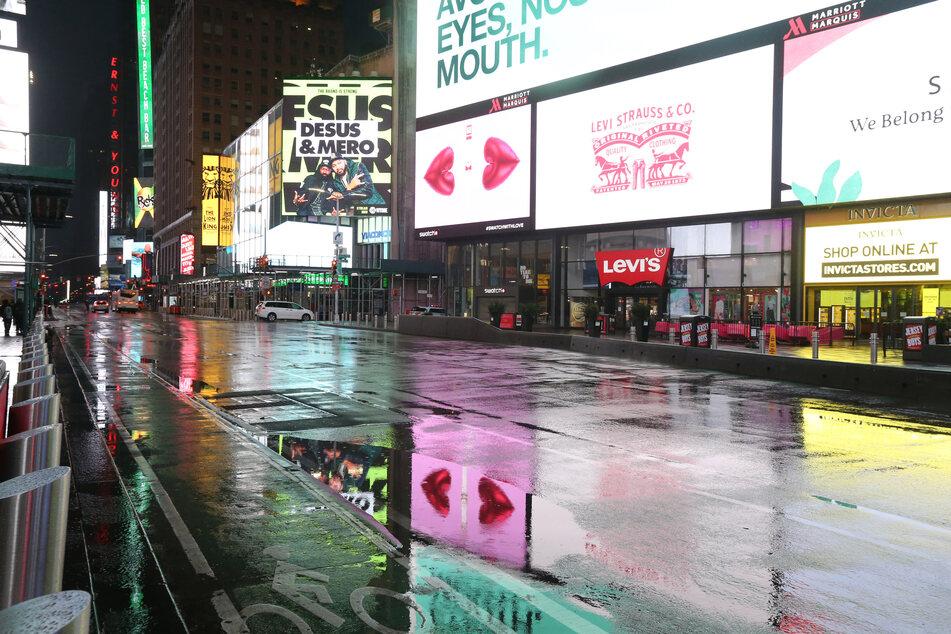 Fast menschenleer ist der Times Square in einer regnerischen Nacht während der Corona-Pandemie.