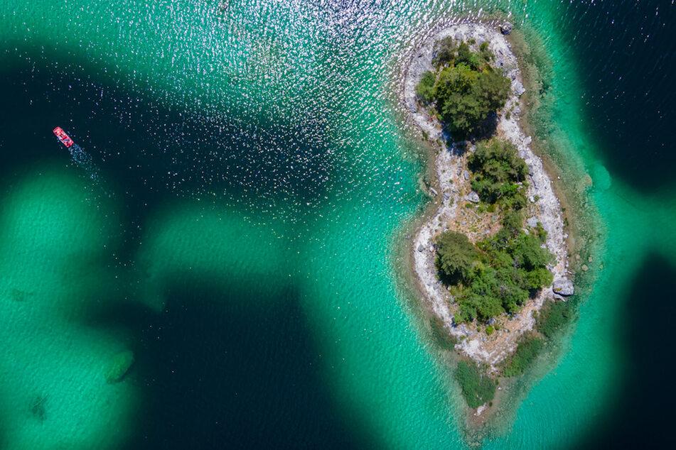 Ausflügler fahren mit einem Tretboot über den in verschiedenen Blautönen schimmernden Eibsee an kleinen Inseln vorbei.