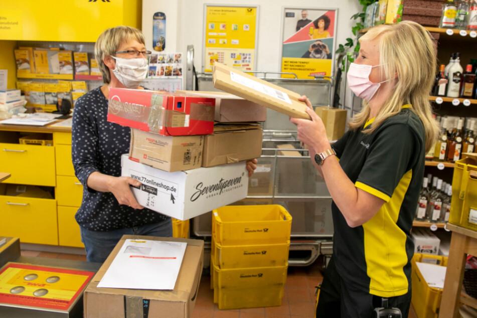 """Eine von insgesamt 1500 sächsischen Postfilialen: In der örtlichen """"Getränke Quelle"""" übergibt die Zustellerin einen Berg Pakete an Verkäuferin Katrin Friebel (53)."""