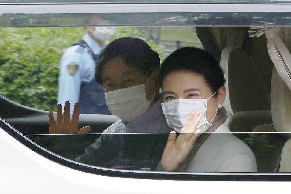Tokio: Kaiser Naruhito und die Kaiserin Masako tragen einen Mundschutz und winken bei ihrer Ankunft am Kaiserpalast.