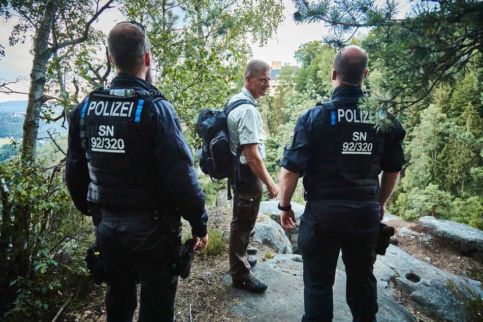 Zwei Polizeibeamte sowie ein Ranger des Nationalparks auf der Suche nach Zündlern.