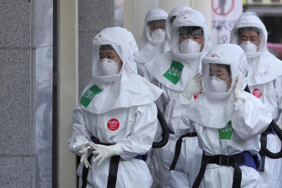 Südkorea, Seoul: Medizinische Mitarbeiter des Dongsan-Krankenhauses treffen in Schutzanzügen zu ihrer Schicht ein.