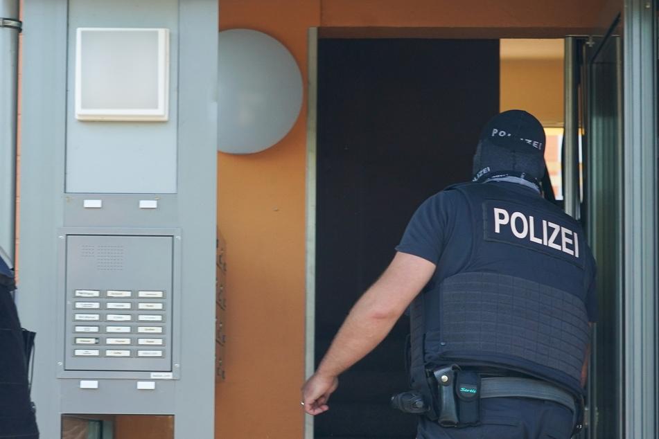 Ein Bundespolizist geht bei einer Razzia in ein Haus in Leipzig-Grünau.