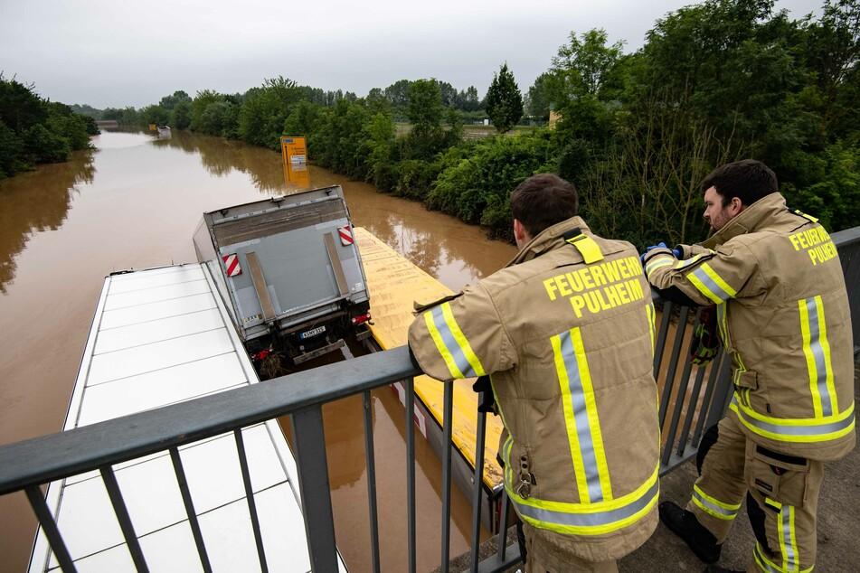 Zwei Feuerwehrleute blicken über die überflutete Bundesstraße 265, die durch Nordrhein-Westfalen und Rheinland-Pfalz führt – die zwei am stärksten betroffenen Bundesländer.