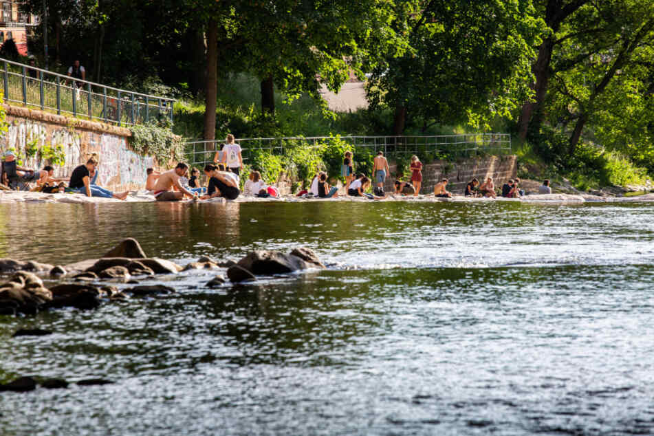 Freiburg: Menschen sitzen an den Ufern der Dreisam und genießen das schöne Wetter.